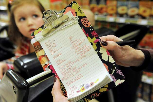 Kara Tubbs of Clifton Park follows a shopping list while grocery shopping with her children on Tuesday, Oct. 14, 2014, at Hannaford in Clifton Park, N.Y. (Cindy Schultz / Times Union) Photo: Cindy Schultz / 10029015A
