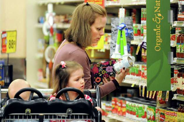 Kara Tubbs of Clifton Park looks over the canned goods while grocery shopping with her children Leo, 1, and Melanie, 3, on Tuesday, Oct. 14, 2014, at Hannaford in Clifton Park, N.Y. (Cindy Schultz / Times Union) Photo: Cindy Schultz / 10029015A