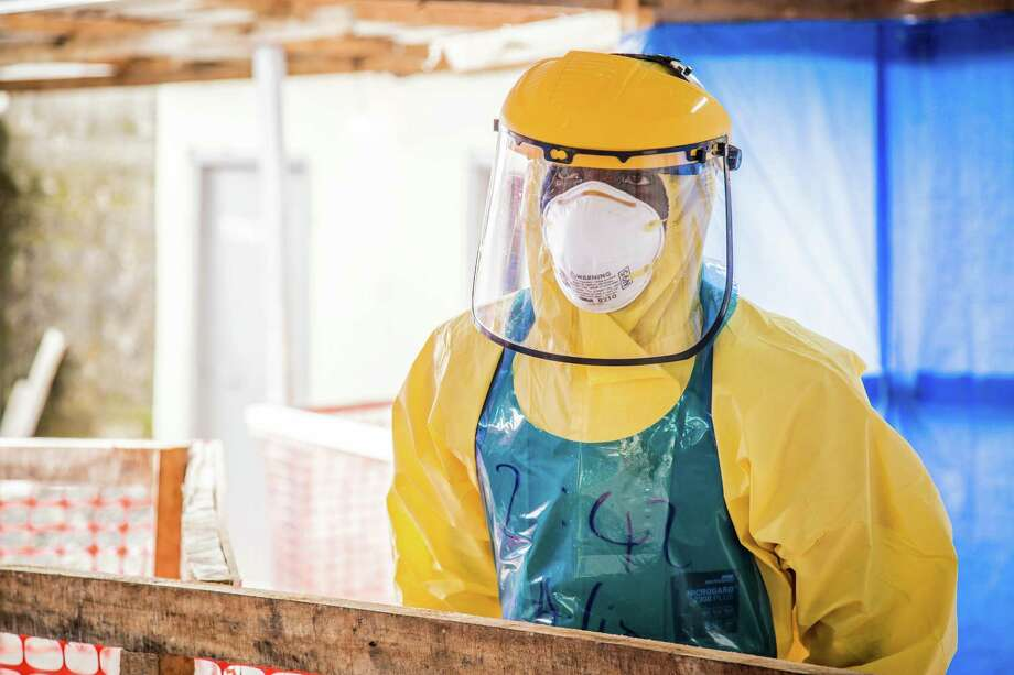 A healthcare worker in protective gear is seen at an Ebola treatment center in the west of Freetown, Sierra Leone, Thursday, Oct. 16, 2014. The deadly Ebola virus has infected two people in what was the last untouched district in Sierra Leone, the government said Thursday, a setback in efforts to stop the spread of the disease in one of the hardest-hit countries. (AP Photo/Michael Duff) ORG XMIT: NIN107 Photo: Michael Duff / AP