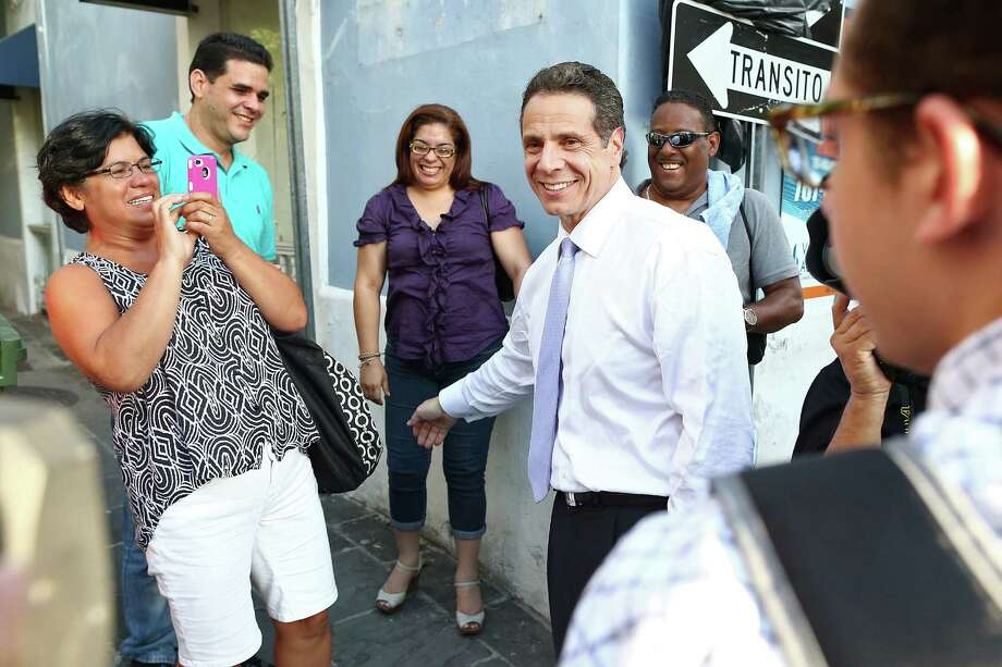 New York Gov. Andrew Cuomo, center, greets people during his visit in San Juan, Puerto Rico, Friday, Oct. 17, 2014. Cuomo took his campaign for a second term to the Caribbean Friday with stops in the Dominican Republic and Puerto Rico - two places with significant ties to the state Cuomo governs. (AP Photo/Jose R. Madera) ORG XMIT: XRA102 Photo: Jose R. Madera / AP