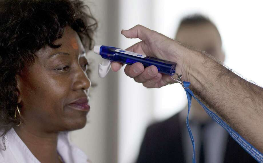 A passenger at an airport in suburban Paris has her temperature taken with an electronic thermometer as part of the Ebola screening there. Photo: Kenzo Tribouillard / Getty Images / AFP