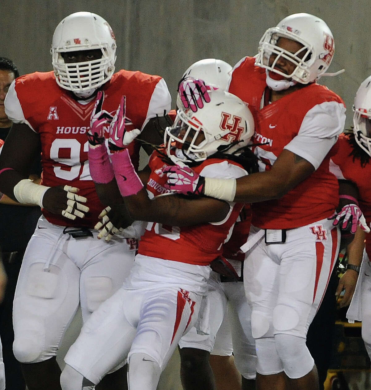 Houston defensive back Trevon Stewart, center, celebrates his 29-yard interception for a touchdown during the first half of a college football game against Temple, Friday, October 17, 2014, at TDECU Stadium in Houston.