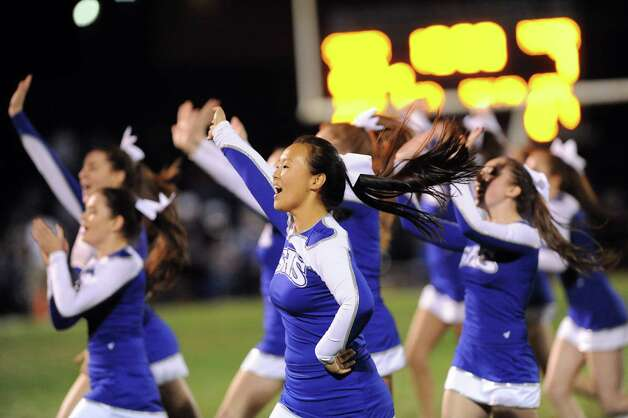 Varsity cheerleader Heidi Hong, 17, center, takes part in the halftime show during their football game against Colonie on Friday, Oct. 17, 2014, at Shaker High in Latham, N.Y. (Cindy Schultz / Times Union) Photo: Cindy Schultz / 00029059A