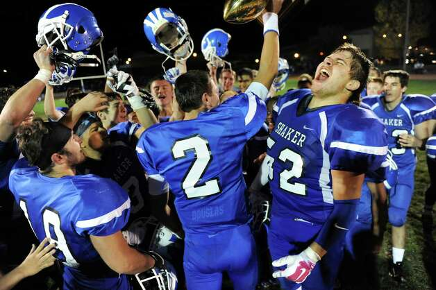 Shaker's Rob Brogden, right, celebrates with his team when they take possession of the Colonie Cup after winning their football game 35-7 over Colonie on Friday, Oct. 17, 2014, at Shaker High in Latham, N.Y. (Cindy Schultz / Times Union) Photo: Cindy Schultz / 00029059A