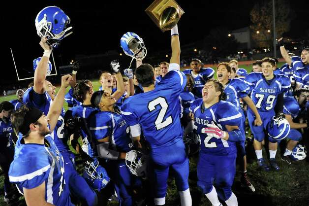 Shaker's quarterback Matt Woods, center, raises the Colonie Cup after winning their football game 35-7 over Colonie on Friday, Oct. 17, 2014, at Shaker High in Latham, N.Y. (Cindy Schultz / Times Union) Photo: Cindy Schultz / 00029059A