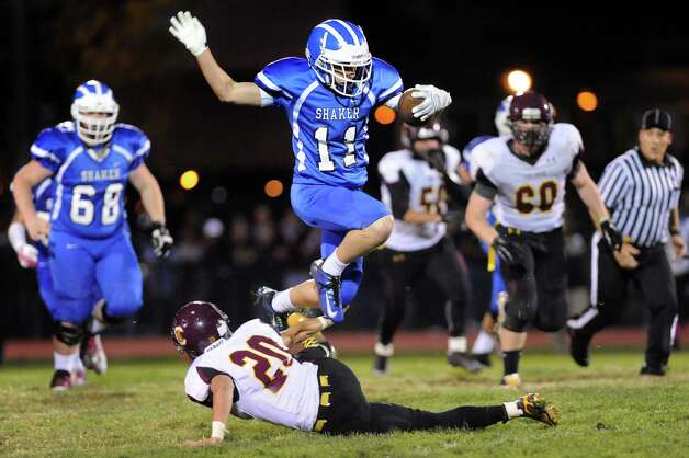 Shaker's Seamus McHugh, center, jumps over Colonie's Will McCann during their football game on Friday, Oct. 17, 2014, at Shaker High in Latham, N.Y. (Cindy Schultz / Times Union) Photo: Cindy Schultz / 00029059A