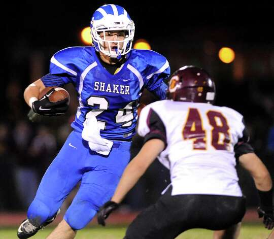 Shaker's Alex Miller, left, gains yards as Taylor Pfaff defends during their football game on Friday, Oct. 17, 2014, at Shaker High in Latham, N.Y. (Cindy Schultz / Times Union) Photo: Cindy Schultz / 00029059A