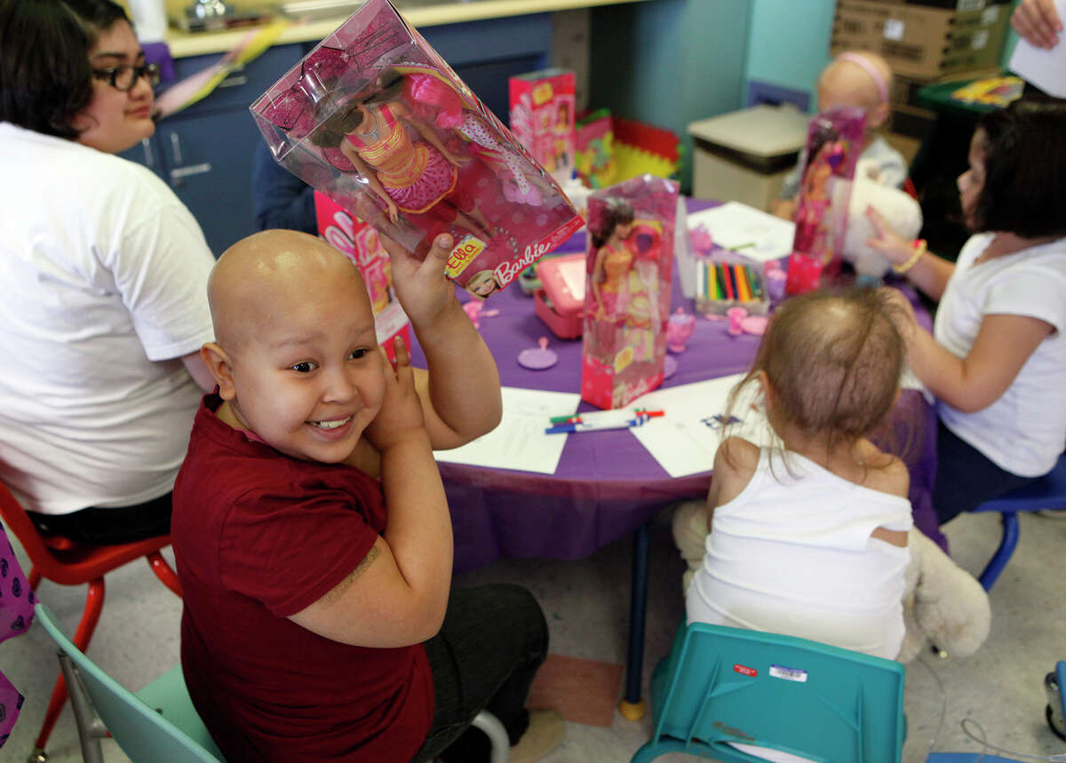 """Heaven Sanchez, 11, shows her parents her new Ella doll Oct. 17, 2014 as she attends an """"Ella Party"""" in which Ella dolls were handed out to those with cancer or their family members by CureSearch at University Hospital's Pediatric Blood and Cancer Center in the playroom of the outpatient clinic. Ella, a friend of Barbie, who is bald and has two wigs, a head scarf and glasses, is produced by Mattel and is not for retail, but is partnered with CureSearch to work with hospitals to get the dolls out for child patients to have a doll that looks like them. Along with getting the dolls, those in attendance also were treated to cupcakes, lemonade, crowns and finger nail painting."""