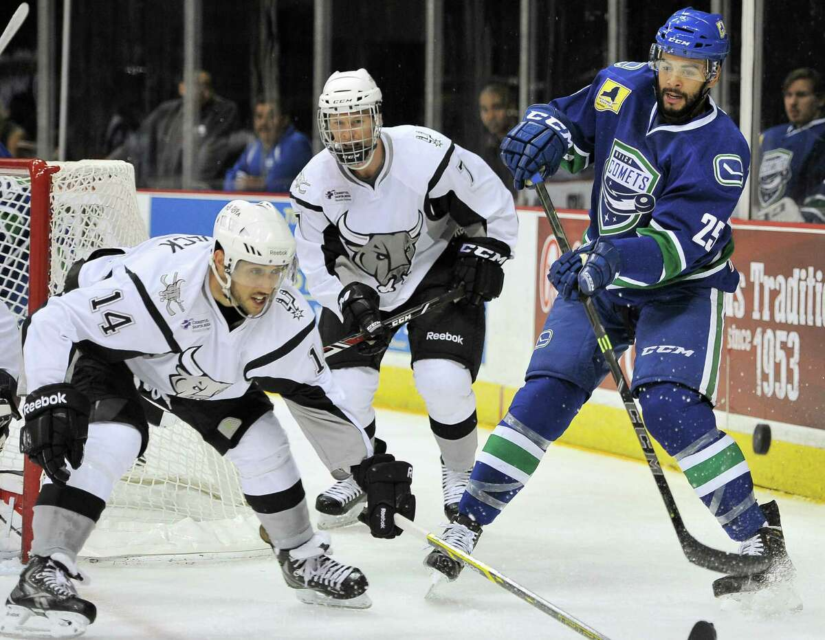 Utica's Darren Archibald (right) passes the puck around Rampage center Vincent Trocheck during the first period.