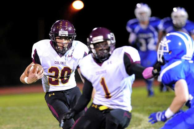 Colonie's Dan Kehrer, left, gets a block from teammate Jay Newsom, center, as he carries the ball to the end zone during their football game against Shaker on Friday, Oct. 17, 2014, at Shaker High in Latham, N.Y. (Cindy Schultz / Times Union) Photo: Cindy Schultz / 00029059A