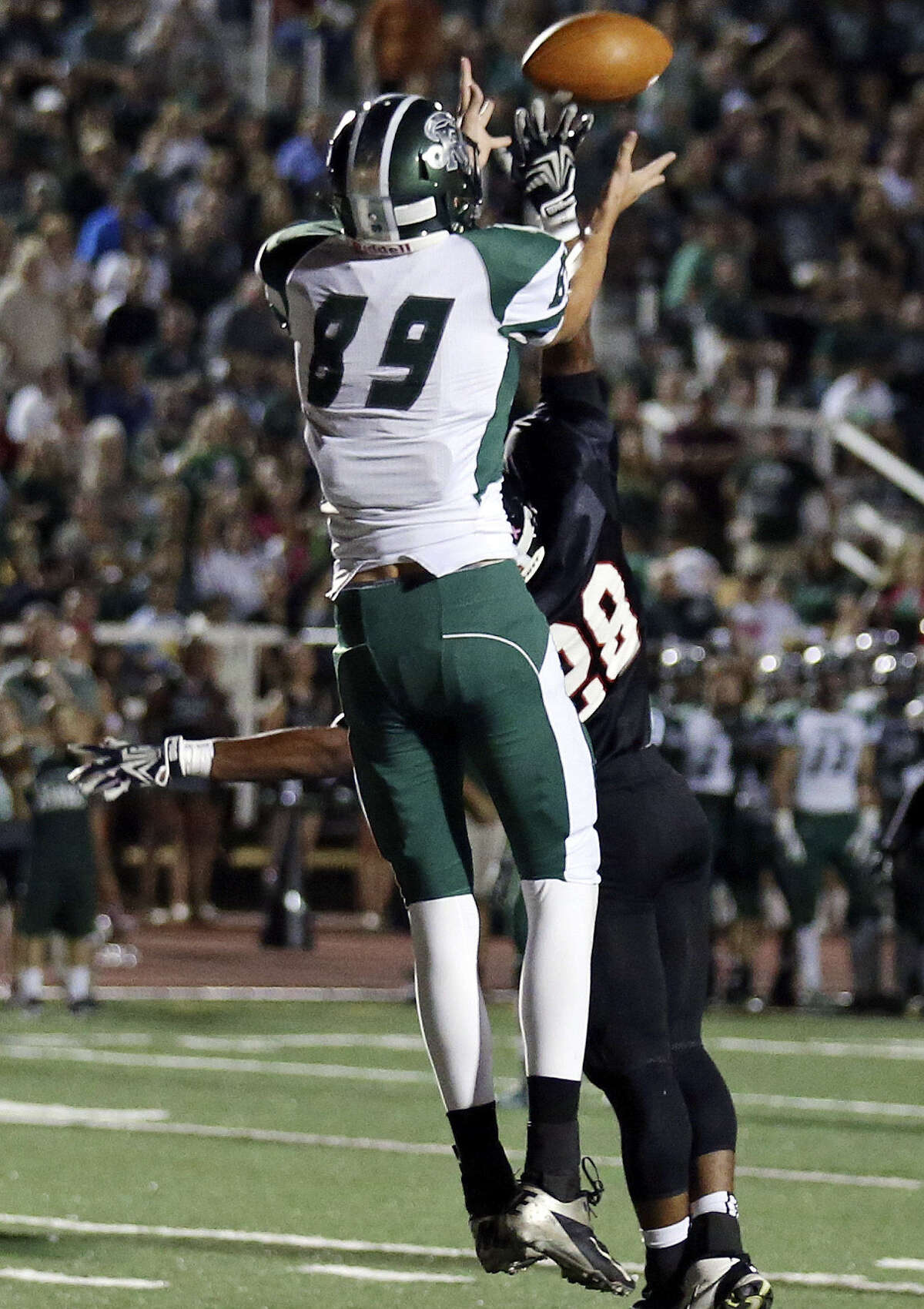 Reagan's Luke Mitchum (89), defended by Churchill's Alex Siminen, goes up for one of his three touchdown catches Friday at Comalander Stadium. He had six catches for 112 yards.