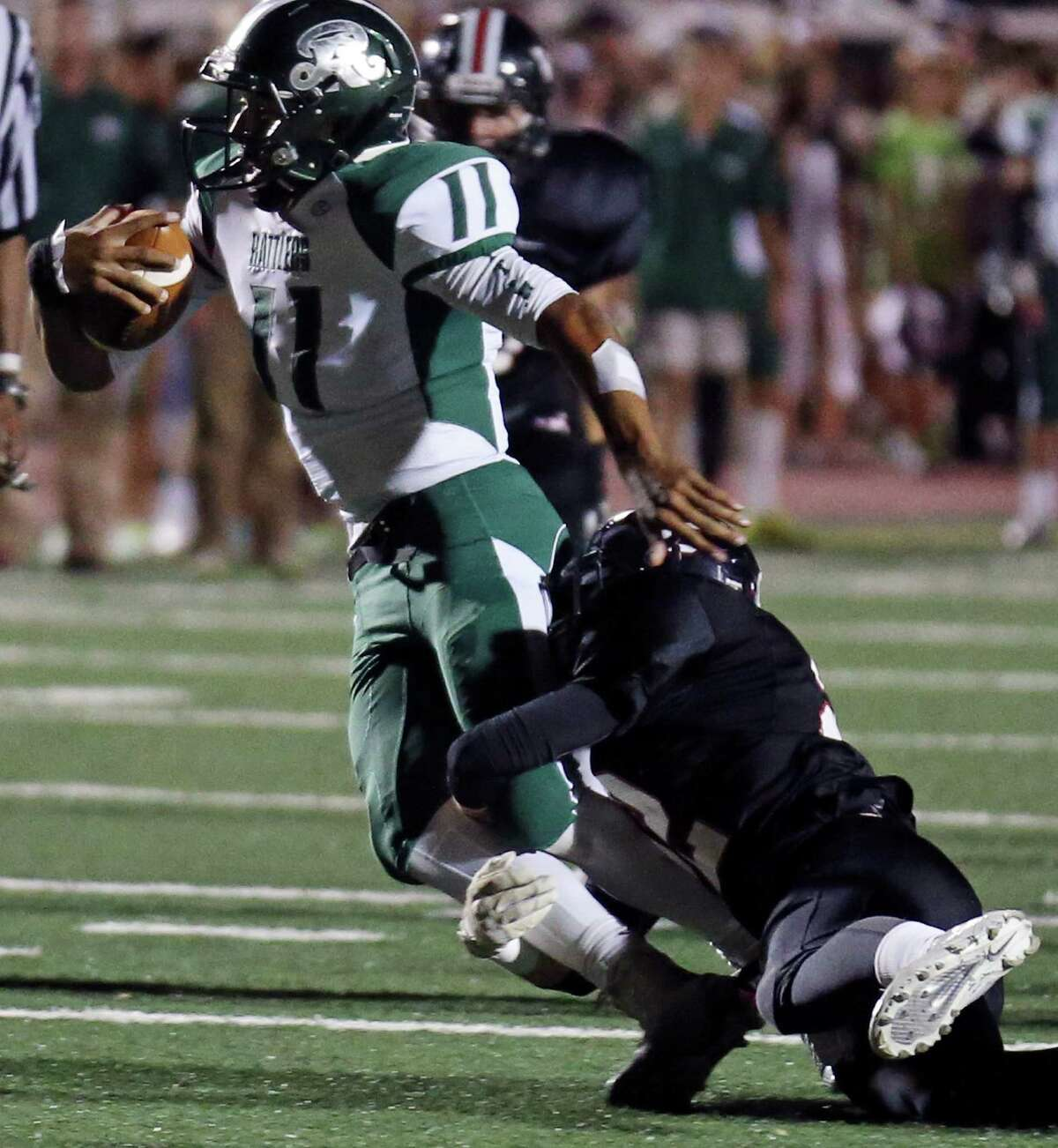 Reagan's Kellen Mond tries to shake the tackle of Churchill's Kyle Pollard during first half action Friday Oct. 17, 2014 at Jerry Comalander Stadium.