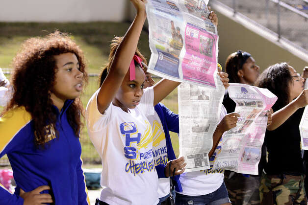 Aryss Harper (white shirt) peaks under the paper as she and fellow Ozen Panther cheerleaders show a lack of interst as the Central Jaguar band plays across the field at the Carroll Thomas Stadium October 17, 2014. Photo by Drew Loker Photo: Drew Loker / ©2014. www.DrewLoker.com