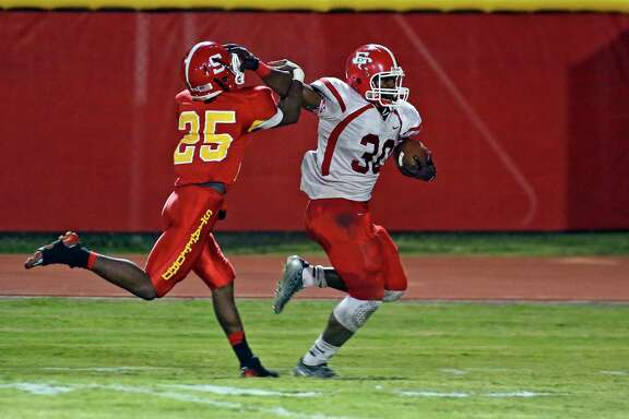 El Campo's Kevin Dove, right, does his best to break free from the grasp of Stafford's Edwin Godfrey during a second-quarter touchdown run Friday night.