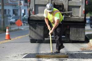Luis Monteiro,50, of Bridgeport, rakes out new asphalt on New Street in Danbury Connecticut, on Friday, October 17, 2014. Monteiro was part of a crew from Burns Construction Company, in Bridgeport, patching the street where Yankee Gas had done utility work.