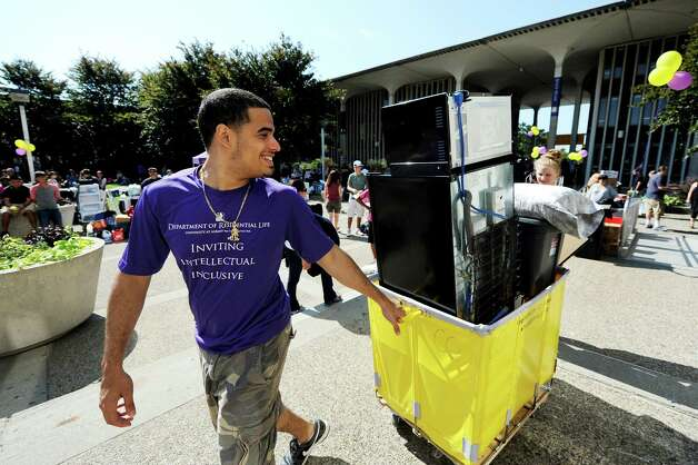 Resident assistant Eric Xiques, 21, helps freshmen move into Eastman Tower on State Quad on Wednesday, Aug. 22, 2012, University at Albany in Albany, N.Y. (Cindy Schultz / Times Union) Photo: Cindy Schultz / 00018846A