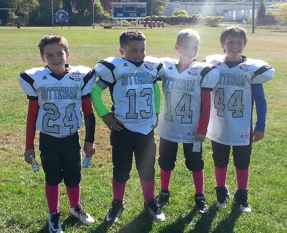 Rotterdam Pop Warner players, from left, Gabe Smith, 8, Camden Banks, 7, Nate Richtmeyer, 8, and Dylan Vandenburg, 8, wear pink socks to support breast cancer awareness during a recent game.