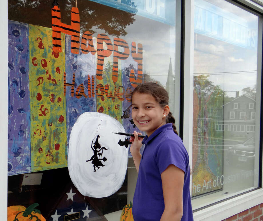 Sophie Alcyon, 10, of Westport paints a Halloween scene on a window at Rockwell Art and Framing as part of the Westport Weston Chamber of Commerce window painting competition Saturday. Photo: Mike Lauterborn / Westport News