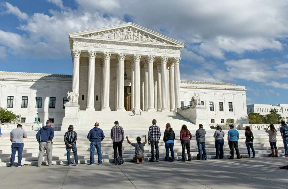 As the Supreme Court begins its new term this week, pro-life advocates hold a prayer vigil on the plaza of the high court in Washington, Saturday, Oct. 4, 2014. The group, Bound 4 Life, has come to the court for ten years to make a silent appeal against abortion.  (AP Photo/J. Scott Applewhite) Photo: J. Scott Applewhite, STF / AP