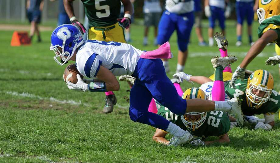 Darien's Colin Minicus dives into the endzone for a touchdown after recovering a loose ball during Saturday's football game at Trinity Catholic High School in Stamford, Conn., on October 18, 2014. Photo: Lindsay Perry / Stamford Advocate