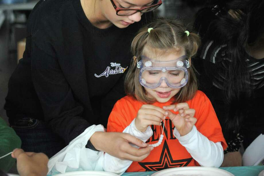 Five-year-old Brooke Haney, center, and her older sister Rachel Haney work on a ulta violet light experiment at the Skidmore College Shem Club display during a National Chemistry Day Celebration at the New York State Museum on Saturday Oct. 18, 2014 in Albany, N.Y.  (Michael P. Farrell/Times Union) Photo: Michael P. Farrell / 00029077A