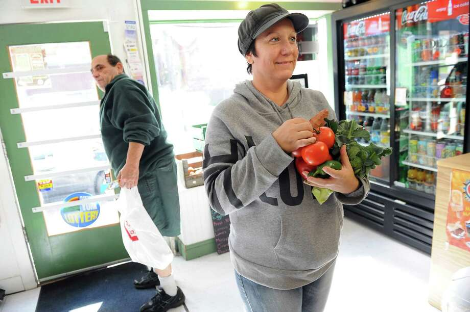Amanda Santiago, right, waits to purchase vegetables on Wednesday, Oct. 8, 2014, at the Can Stop Redemption Center and Groceries Inc. in Troy, N.Y. The neighborhood store receives a weekly shipment of fresh fruits and vegetables from Capital District Community Gardens. (Cindy Schultz / Times Union) Photo: Cindy Schultz / 10028905A
