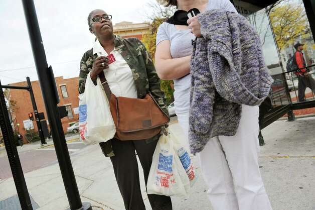 Eva Clark of Albany waits for the bus after shopping at Price Chopper on Thursday, Oct. 16, 2014, in Albany, N.Y. Clark said she takes two buses to back and forth from Ida Yarbrough Homes to the grocery store. Sometimes she shares a taxi with other tenants, especially when the weather's bad. (Cindy Schultz / Times Union) Photo: Cindy Schultz / 00029055A