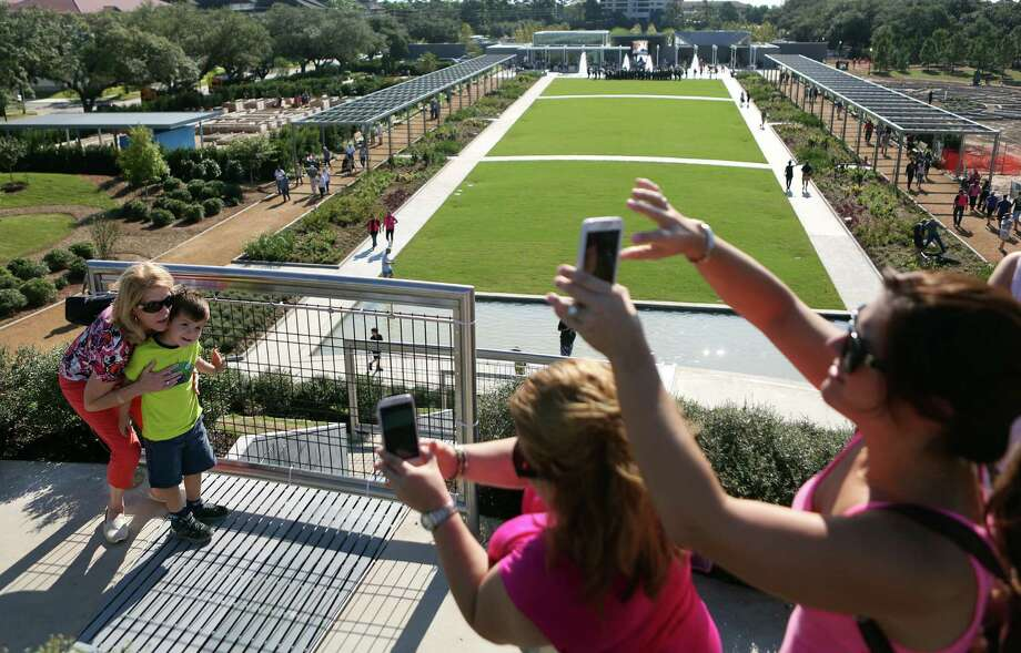 Diana Barnes and Sebastian De La Garza are photographed by Iris De La Garza on top of the 30' Garden Mount that overlooks the Great Lawn at The McGovern Centennial Gardens which is open to the public for one day until the project is completely finished on Saturday, Oct. 18, 2014, in Houston.  Photo: Mayra Beltran, Houston Chronicle / © 2014 Houston Chronicle