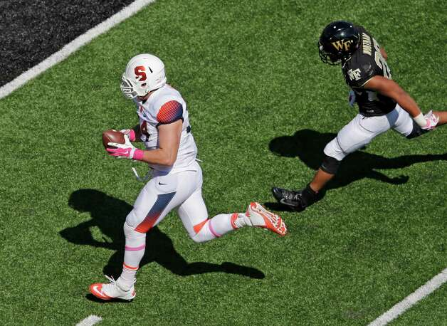 Syracuse's Robert Welsh (94) returns an interception for a touchdown as Wake Forest's Dezmond Wortham (20) chases during the first half of an NCAA college football game in Winston-Salem, N.C., Saturday, Oct. 18, 2014. (AP Photo/Chuck Burton) ORG XMIT: NCCB103 Photo: Chuck Burton / AP