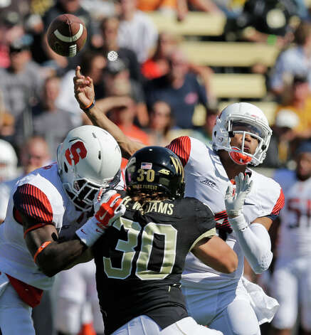 Syracuse's AJ Long (4) throws a pass under pressure from Wake Forest's Hunter Williams (30) during the second half of an NCAA college football game in Winston-Salem, N.C., Saturday, Oct. 18, 2014. Syracuse won 30-7. (AP Photo/Chuck Burton) ORG XMIT: NCCB114 Photo: Chuck Burton / AP