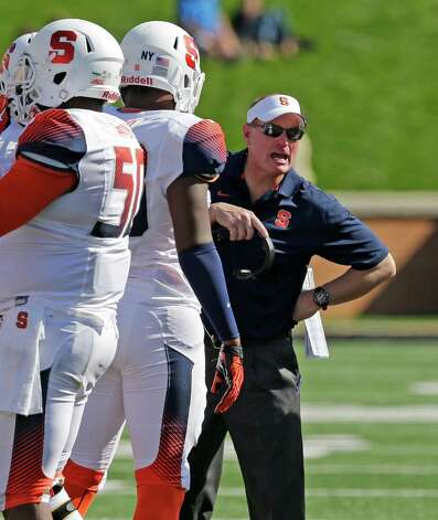 Syracuse head coach Scott Shafer, right, talks to his team during a timeout in the second half of an NCAA college football game against Wake Forest in Winston-Salem, N.C., Saturday, Oct. 18, 2014. Syracuse won 30-7. (AP Photo/Chuck Burton) ORG XMIT: NCCB113 Photo: Chuck Burton / AP