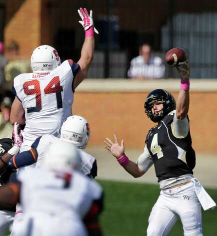 Wake Forest's Tyler Cameron (4) tries to throw a pass over Syracuse's Robert Welsh (94) during the second half of an NCAA college football game in Winston-Salem, N.C., Saturday, Oct. 18, 2014. Syracuse won 30-7. (AP Photo/Chuck Burton) ORG XMIT: NCCB110 Photo: Chuck Burton / AP