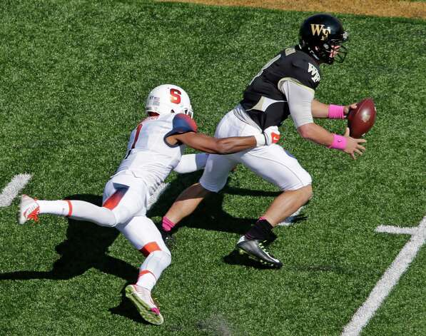 Wake Forest's Tyler Cameron, right, is sacked by Syracuse's Julian Whigham (1) during the first half of an NCAA college football game in Winston-Salem, N.C., Saturday, Oct. 18, 2014. (AP Photo/Chuck Burton) ORG XMIT: NCCB104 Photo: Chuck Burton / AP