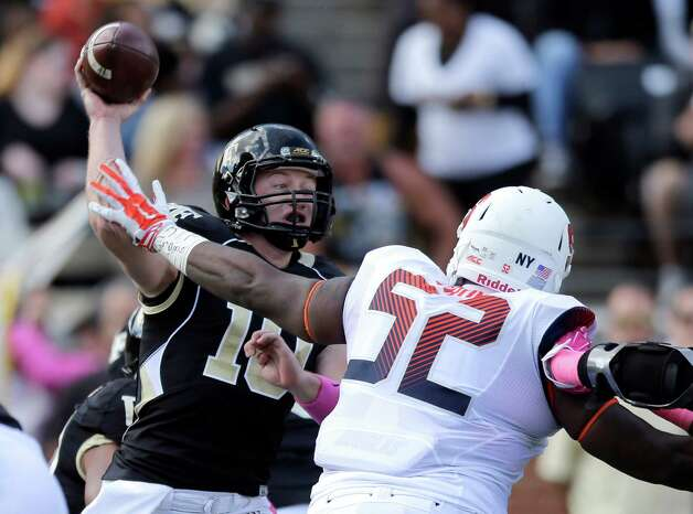 Wake Forest's John Wolford (10) throws a pass under pressure from Syracuse's Eric Crume (52) during the first half of an NCAA college football game in Winston-Salem, N.C., Saturday, Oct. 18, 2014. (AP Photo/Chuck Burton) ORG XMIT: NCCB105 Photo: Chuck Burton / AP