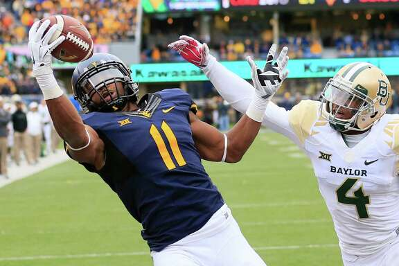 West Virginia's Kevin White, left, beats Xavien Howard for the go-ahead TD in the fourth quarter. Howard also was called for four pass interference penalties.