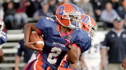 Danbury's quarter back Anferny Ith (2) keeps the ball on the option during the Staples and Danbury High School boys football game on Saturday, October, 18, 2014, in Danbury, Conn.