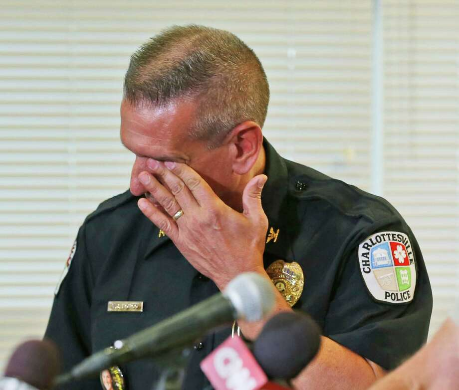 Charlottesville Police Chief, Tim Longo,  wipes his eyes as he and Albermarle County police Col. Steve Sellers, brief the media on the discovery of remains in Albermarle County during a news conference in Charlottesville, Va., Saturday, Oct. 18, 2014. Searchers found human remains on Saturday that could be those of a University of Virginia sophomore who has been missing since Sept. 13, police said. Further forensic tests are needed to confirm whether the remains are those of Hannah Graham,  Chief Longo told a news conference.  (AP Photo/Steve Helber) Photo: Steve Helber, STF / AP