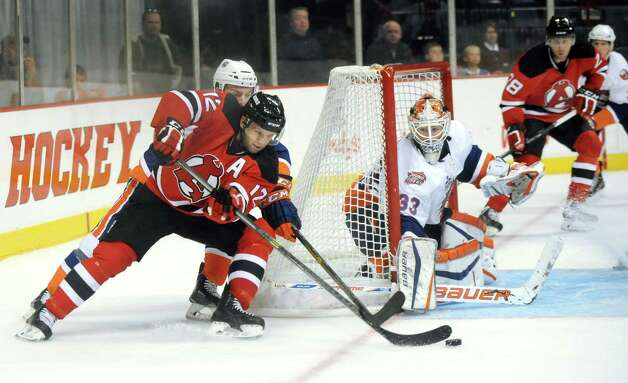 Devils Tim Sestito, left, brings the puck around as Tigers goalie David Leggio, center, defends the net during their hockey game on Saturday, Oct. 18, 2014, at Times Union Center in Albany, N.Y. (Cindy Schultz / Times Union) Photo: Cindy Schultz / 10028979A