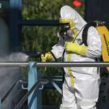 A first responder wears a full biohazard suit while spraying a disinfecting solution on the railing at the Dallas Area Rapid Transit (DART) White Rock Station after a woman with Ebola-like symptoms fell ill at the station October 18, 2014 in Dallas, Texas. The woman reportedly stayed in the same apartment complex as Thomas Eric Duncan, the Liberian who was the first patient diagnosed with Ebola in the United States and who died on October 8.