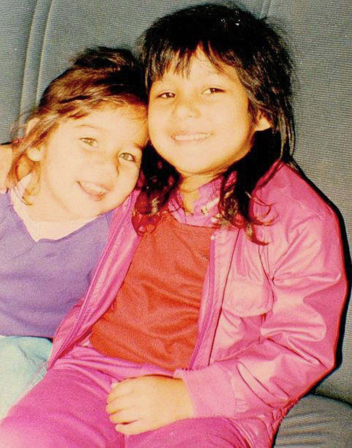 Melissa Garcia, left, leans against her cousin, Natalie Ochoa, in Houston at an early age.
