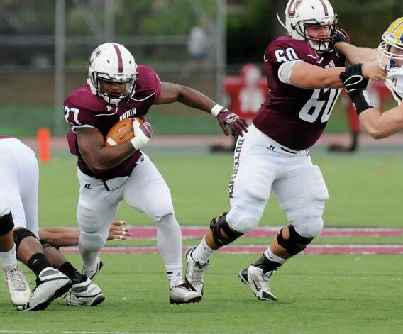 Union's Darnel Thomas (27) gets a block by teammate Tom Grimmer (60) as he runs the ball against Western New England during the first half of an NCAA college football on Saturday, Oct. 18, 2014, in Schenectady, N.Y. (Hans Pennink / Special to the Times Union) ORG XMIT: HP105 Photo: Hans Pennink / Hans Pennink