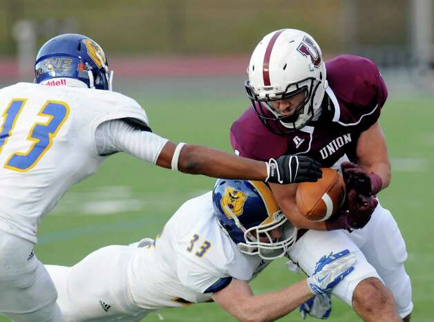 Western New England's Isaiah Berrios (13) and Sam Olsson (33) cause Union's Kyle Reynolds (1) to fumble the ball during the first half of an NCAA college football on Saturday, Oct. 18, 2014, in Schenectady, N.Y. (Hans Pennink / Special to the Times Union) ORG XMIT: HP110 Photo: Hans Pennink / Hans Pennink