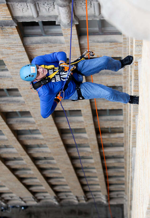 Tom Jaeger rappels down the 22-story Milam Building with the help of Navy Petty Oficer 2nd Class Pete Voelz (from top) and Ady Geda, and Tela Mange in Over the Edge, an event in support of 9,500 Special Olympics Texas athletes in the San Antonio area, on Saturday, Oct. 18, 2014. The third annual event of Over the Edge was presented by Clear Channel Outdoor, Clear Channel Media and Entertainment and KSAT 12 and raised approximately $17,000. MARVIN PFEIFFER/ mpfeiffer@express-news.net Photo: Marvin Pfeiffer / San Antonio Express-News / Express-News 2014