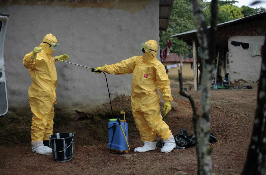 One medical worker sprays another after they loaded six patients suspected of having Ebola into an ambulance in Freeman Reserve, north of Liberia's capital, Monrovia, on Sept. 30. Photo: Jerome Delay / Associated Press File Photo / AP