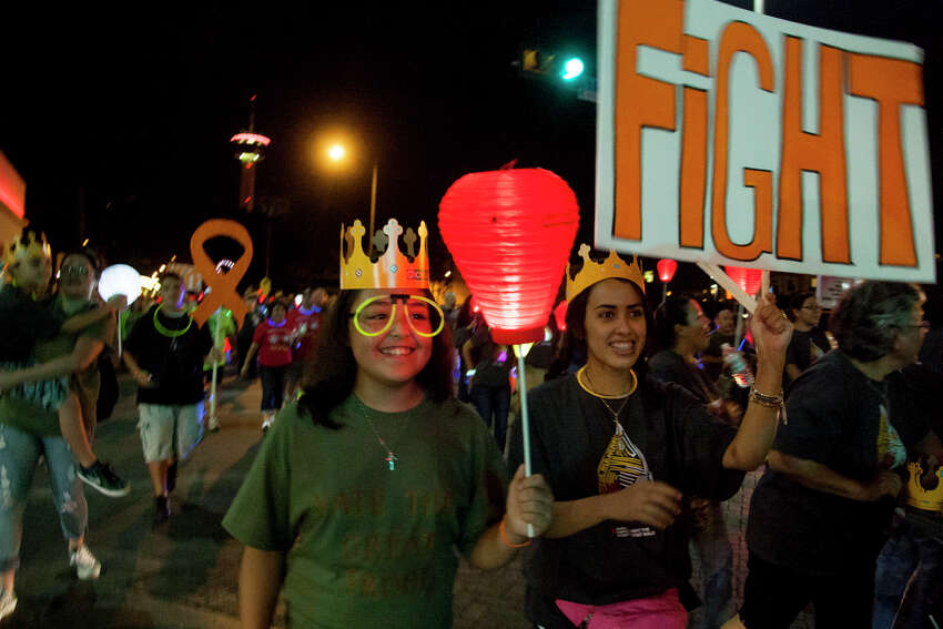 Elizabeth Garcia, 10, and Caitlin Guarnero, 17, walk during the Light The Night Walk fundraising campaign of the Leukemia and Lymphoma Society Saturday October 18, 2014 at La Villita. The money raised by the campaign help fund advanced therapies.