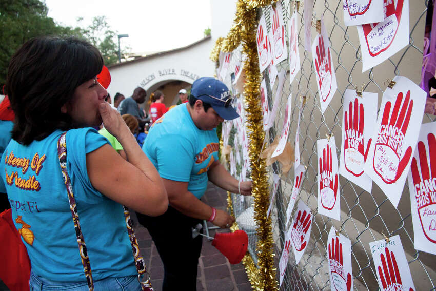 Linda Hurtado looks at her husband's name along a fence honoring the Light The Night Walk fundraising campaign of the Leukemia and Lymphoma Society Saturday October 18, 2014 at La Villita. The money raised by the campaign help fund advanced therapies.
