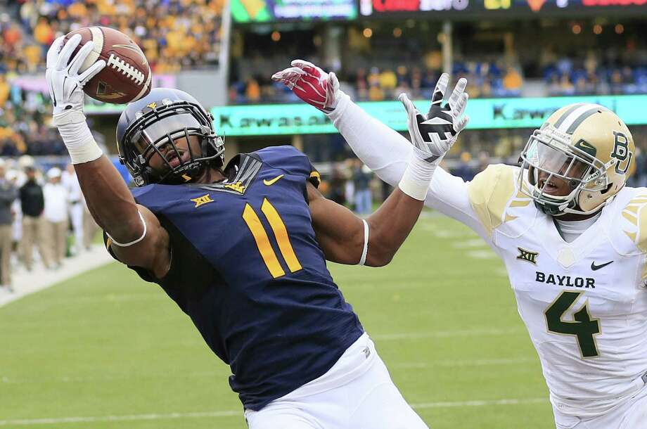 West Virginia's Kevin White catches a 12-yard TD pass in the fourth quarter despite the efforts of Baylor's Xavien Howard. Photo: Chris Jackson / Associated Press / FR170573 AP