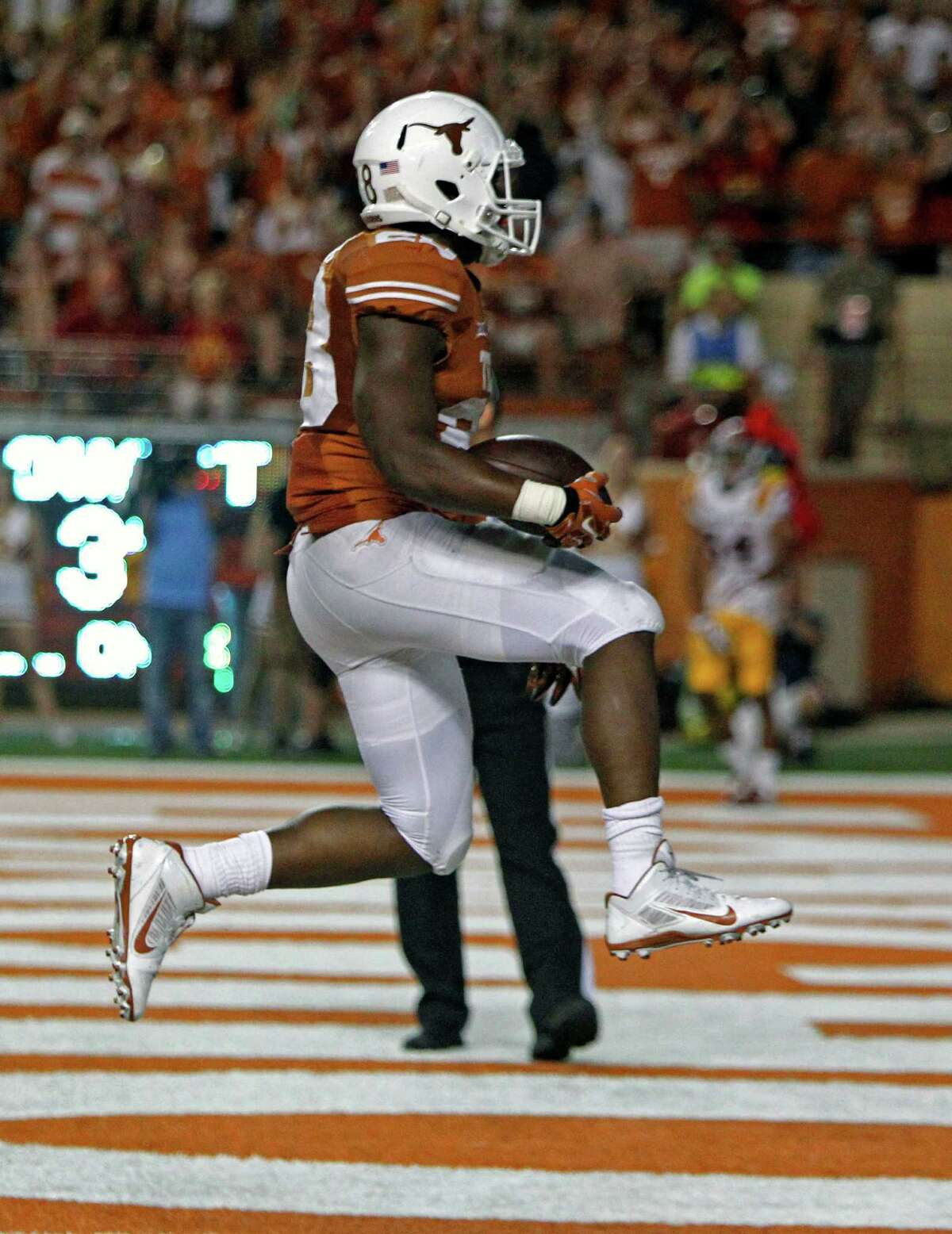 Texas running back Malcolm Brown jumps into the end zone after scoring a touchdown during the fourth quarter of an NCAA college football game against Iowa State in Austin, Texas, Saturday, Oct. 18, 2014. Texas won 48-45. (AP Photo/Michael Thomas)