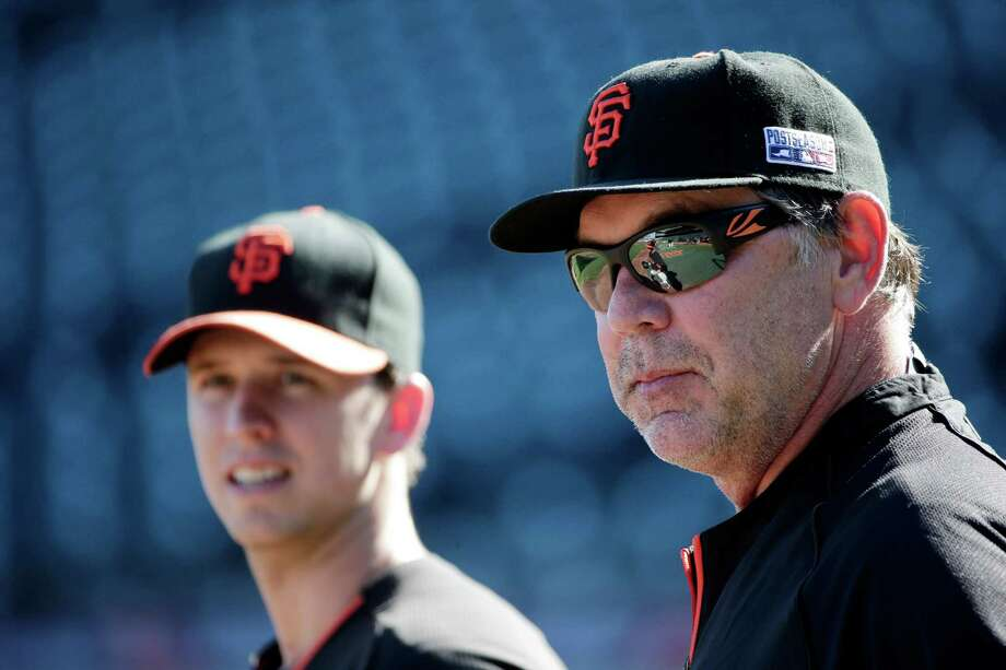 San Francisco Giants manager Bruce Bochy, right, watches batting practice alongside Buster Posey, at left, during a team workout on Saturday, Oct. 18, 2014, in San Francisco.  The Giants are scheduled to play the Kansas City Royals in Game 1 of baseball's World Series on Tuesday, Oct. 21, in Kansas City.  (AP Photo/Marcio Jose Sanchez) Photo: Marcio Jose Sanchez / Associated Press / AP