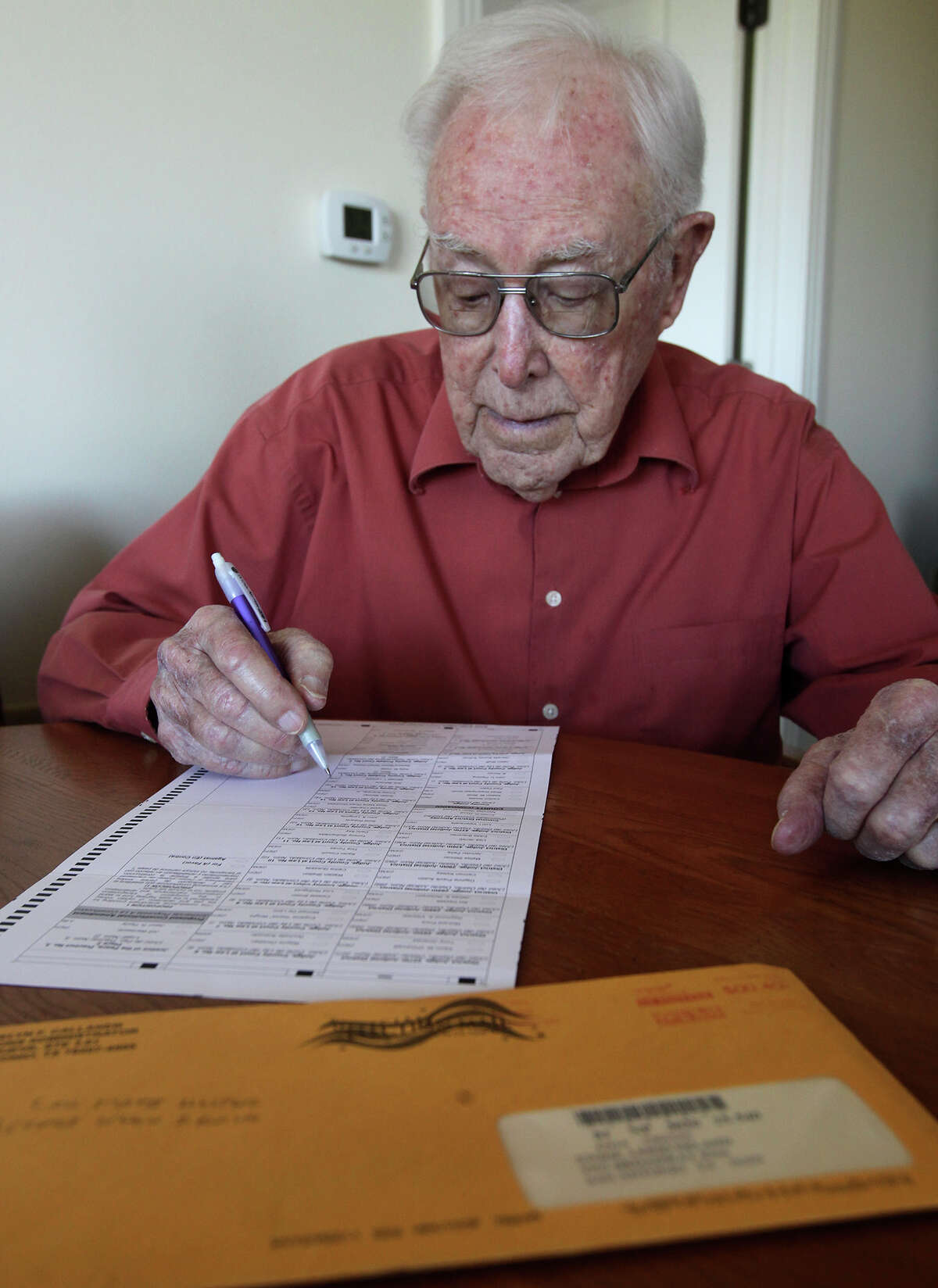 Lee Stone,93, looks over his mail in voting ballot Wednesday October 15, 2014. Stone lives at the Village at Incarnate Word.